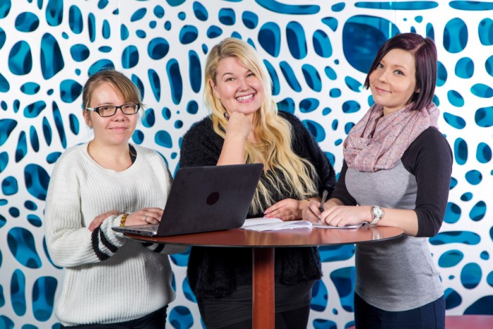 The students of business administration stand behind a table. Photo: Olli Häkämies
