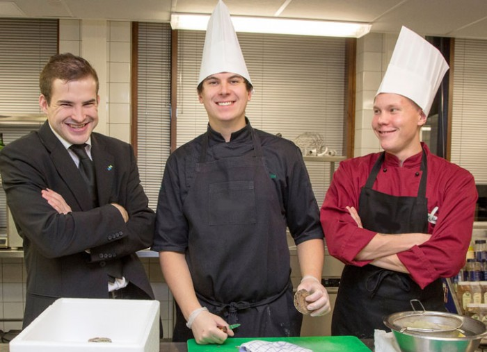 Two students of hospitality management with a cook hat stand with their teacher stand in a kitchen of a restaurant. Photo: Olli Häkämies