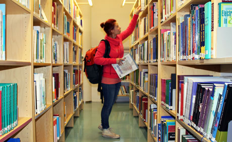 Student is taking a book from the shelf in the library.