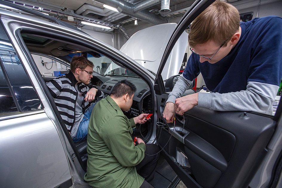 Engineering students install components of an electric car.
